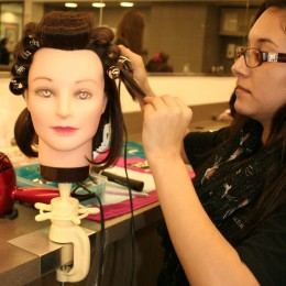 """Cynthia Velazquez prepares for the March """"Art of Hair"""" show on her mannequin, which was held in the Hayden Memorial Library."""