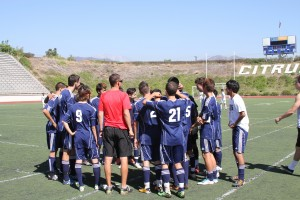 The Owls men's soccer team has a team huddle before the match.