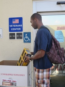 Sean Horace, 23, kinesiology major, stops by the Veterans Center to donate a toy truck set into the Toys for Tots collection bin. (Sarah Cha/ Citrus College Clarion)