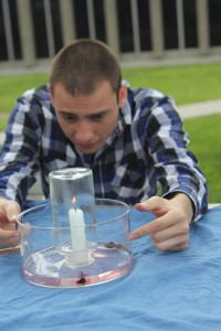 "Athanasios Klovtsiniotis, 21, demonstrates a ""candle trick"" at the Chemistry Club booth on March 11 during Club Rush. As the glass beaker smothers the flame out the water rises into the glass. (Jessica Soto/Citrus College Clarion)"