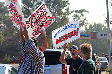 Protestors assembled outside the entrance to Frank G. Bonelli Park getting the attention of cars on the 57 North freeway. (Evan Solano/Clarion)
