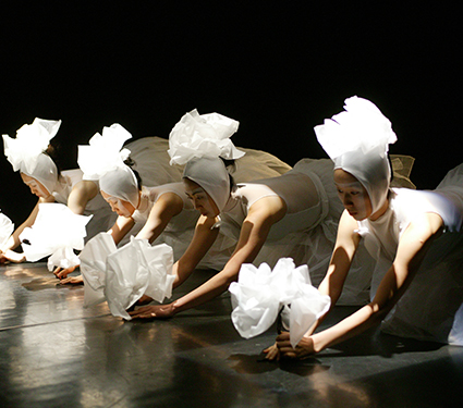 "The second act ""Enlightenment"" begins with only the sight and sound of a troupe of female dancers slowly scrunching pieces of paper together.  (Courtesy KMP Artists)"