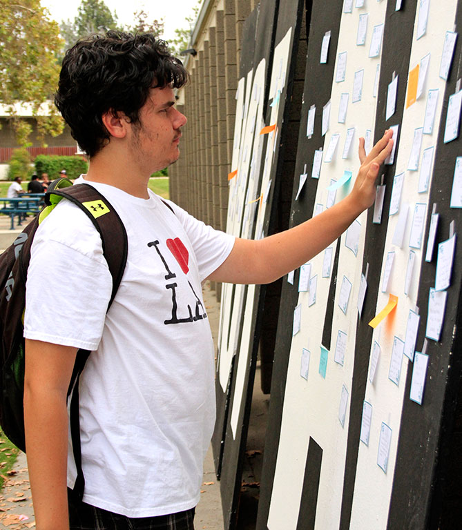 Cameron Sparks, 19, elementary education major posts a message on the suicide awareness wall next to the Student Center. The wall was an effort to promote Suicide Awareness Day. (Megan Bender/Clarion)