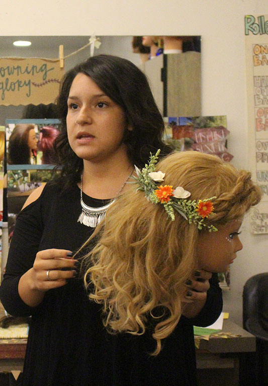 Andrea Aguilera, 22, cosmetology student, explaining her crown themed and nature influenced hair styles to the rest of the class for the cosmetology final. (David Rosales/Clarion)