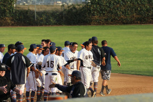 Dominic Baca (right) emerges from the celebration mob after his game-winning hit. The Owls defeated San Bernadino Valley College 7-6 on Feb. 23.