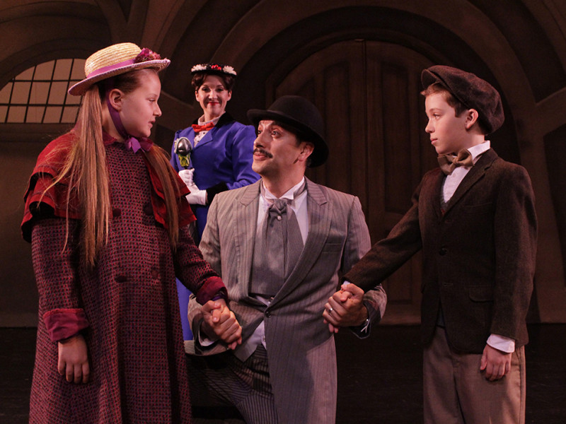 Mary Poppins, played by Kylie Molnar, looks on as George Banks, played by Roger Cobian embraces the Banks children, played by Brooklyn Vizcarra and Benjamin Lightfoot in the Haugh Perfomring Arts Center (Photo courtesy of Haugh Performing Arts Center)