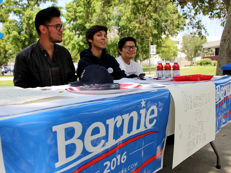(From left to right) Matthew Luna, Rasses Montes and Erik Lopez encourage students to register to vote, discuss their political preferences and maybe vote for Bernie Sanders. The three are an uofficial group that set up a campaign table May 10 in the Campus Center Mall.
