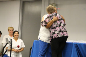 Emma Collins hugs professor Wong while the rest of the nurses wait in line to receive their nursing pins at the Vocational Nurses Pinning ceremony Aug. 25 in the Campus Center Mall.