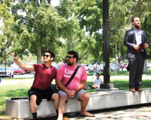 Students and best friends Jacob Gomez and Ryan Grosjean ask preacher Sebastian Bryan to take a selfie with them during his open air preaching Aug. 25 in the Campus Center Mall. Bryan was speaking out against homosexuality when Gomez and Grosjean held hands and sat down next to him in protest. (Evan Solano/Clarion)