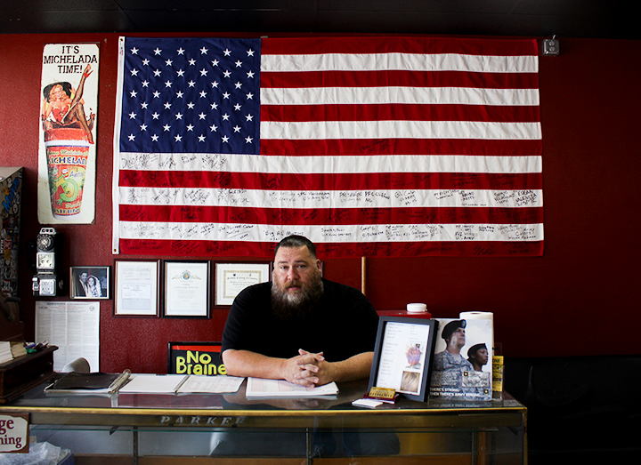Mike Kane, owner of Hellboys Greaser Garage Barbershop sits at the front desk where he awaits customers and also makes appointments.